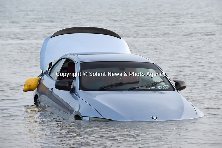 Pictured:  The car was completely submerged by sea water.<br /> <br /> An unlucky driver left their sports car parked by the sea only for it to roll down a slipway and end up submerged by the tide.  Dog walkers and passersby noticed the flashy BMW stuck in the mud early this morning.<br /> <br /> The silver convertible 3 series - complete with sporty bucket seats and worth approximately £7,000 - was later covered by seawater in Southampton Water, Hants.  SEE OUR COPY FOR DETAILS.<br /> <br /> © Simon Czapp/Solent News & Photo Agency<br /> UK +44 (0) 2380 458800