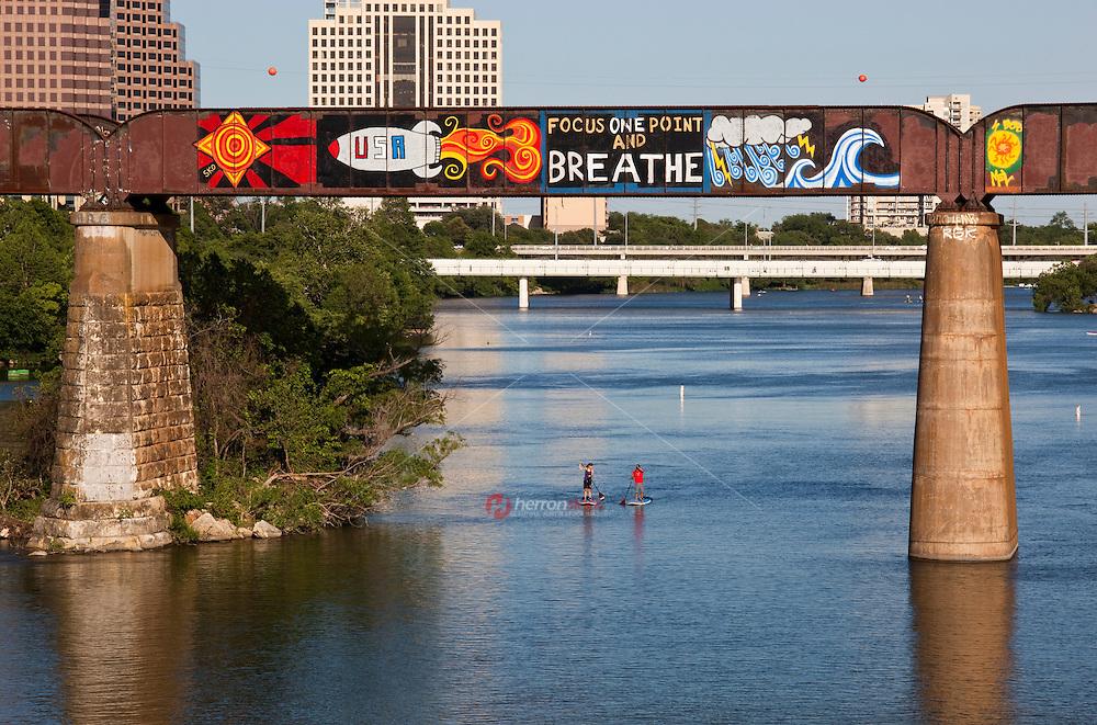 Graffiti outlines the Union Pacific Train Trestle Bridge over Lady Bird Lake Austin as couple Paddle Boards below