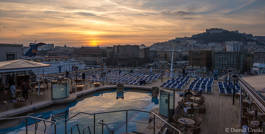 Travel Photograph of a ship deck view with pool reflections of a golden sunset in Naples Italy.<br />