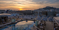 Travel Photograph of a ship deck view with pool reflections of a golden sunset in Naples Italy.<br /> This scene was taken from the Nordam cruise ship.