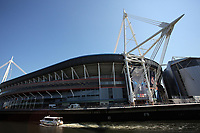 Pictured: A small cruise boat travels in river Taff as workers in abseiling gear install a banner outside the National Stadium of Wales (aka Principality Stadium) Thursday 25 May 2017<br />