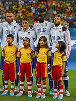 A young mascot looks up at Mario Balotelli of Italy