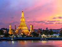 Wat Arun Temple glows from across the river at sunset.