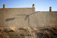 The shadow of a small wind turbine falls on the wall of a farm on the Xilamuren grasslands that dominate the north of the Inner Mongolian capital, Hohhot.