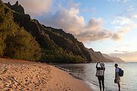 At sunset, a couple admires the view of Na Pali Coast and takes a photograph at Ke'e Beach, northern Kaua'i.