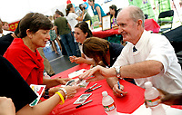 Arkansas Democrat-Gazette/JASON IVESTER 09-12-08<br />Former Arkansas track and field coach John McDonnell (right) signs an autograph for Dianne Zimmerman (left) of Fayetteville along with Olympics athletes April Steiner-Bennett, Christin Wurth-Thomas and Calvin Davis Friday at the United Way of Northwest Arkansas Community Volunteer Event at the Procter & Gamble office in Fayetteville. Zimmerman was getting the autographs for her grandson, Brad Zimmerman of Chicago, who is a Razorback fan.