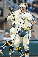 Michigan Wolverines catcher Joe Donovan (0) celebrates with teammate Aka Thomas (4) after his eighth inning home run against the Vanderbilt Commodores during Game 1 of the NCAA College World Series Finals on June 24, 2019 at TD Ameritrade Park in Omaha, Nebraska. Michigan defeated Vanderbilt 7-4. (Andrew Woolley/Four Seam Images)