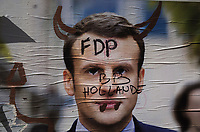 """France. Ile de France. Paris. Partially torn campaign poster of French presidential election candidate Emmanuel Macron for the centrist party """"En Marche"""". A graffiti with the written words, Baby from french president François Hollande, and a drawing with two horns. 22.04.17 © 2017 Didier Ruef"""