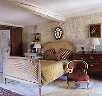 A Louis XVI bed is accompanied by a gilded 'crapaud' chair covered in velvet in this bedroom with a stone floor and walls