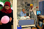 """A Palestinian woman holds a balloon next to Mustafah Mshasha, a Palestinian boy from the Old City of Jerusalem who plays with clown Dudi (Dudy Barashi an Israeli  medical clown who works in Hadassah member of a group call """"Dream Doctor"""") as he receives chemotherapy at the Oncology Day Care unit at Hadassah Ein Karem hospital. ..Mustafa suffers from Leukemia and has been treated in the Children Oncology Unit. Photo by Quique Kierszenbaum  .."""
