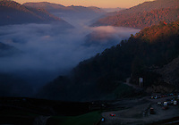Morning fog fills a valley below a small mountaintop removal mine.