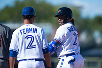 Surprise Saguaros third baseman Vladimir Guerrero Jr. (27), of the Toronto Blue Jays organization, talks to first base coach Andy Fermin (2) after hitting a single during an Arizona Fall League game against the Salt River Rafters on October 9, 2018 at Surprise Stadium in Surprise, Arizona. The Rafters defeated the Saguaros 10-8. (Zachary Lucy/Four Seam Images)