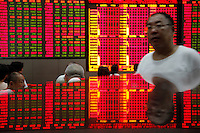 A stock display is reflected on a tabletop while investors monitor trade stocks at a securities exchange house in Shanghai, China. The Shanghai Stock Exchange (SSE) is one of the three stock exchanges operating independently in the People's Republic of China, the other two are the Shenzhen Stock Exchange and the Hong Kong Stock Exchange. It is the world's sixth largest stock market by market capitalization at US$2.4 trillion as of Aug 2010..17 Aug 2010