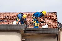 Milano, periferia nord. Lavori di manutenzione sul tetto di un palazzo residenziale --- Milan, north periphery. Maintenance work on the roof of a residential building