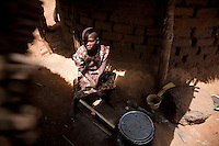 "Cavine helps her mother with household chores and keeps the cooking fires going when asked..Cavine, age 10, was the first child  started on ARV's by MSF in Madi Opei, Uganda. Her mother sought treatment for her at a variety of  hospitals around Madi Opei before  she was tested and treated by MSF. Without treatment she would surely have died her mother said. Now she has gained weight and  feels good. ""When i look at my picture there i see someone who is healthy and i dont see any sick patient there"" Cavine said when shown these pictures."
