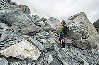 Tramper among huge boulders in Copland Valley admiring mountains, Westland National Park, West Coast, World Heritage Area, South Westland, New Zealand