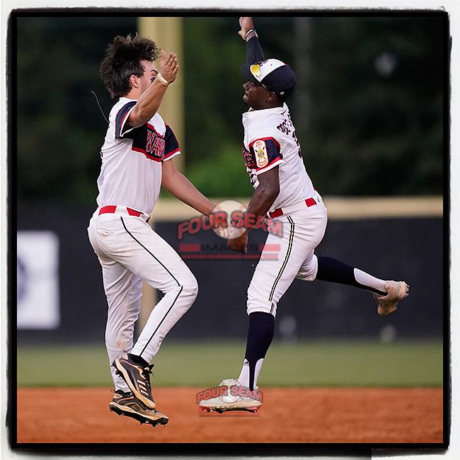 Garrett Dill (15) and Darius Griffin (2) of the Greer Warhawks Post 115 jump to celebrate a 19-4 win over Williamston Post 121 in a South Carolina American Legion state tournament playoff game on Tuesday, July 27, 2021, at Stevens Field in Greer, South Carolina. Greer won, 19-4. (Tom Priddy/Four Seam Images)