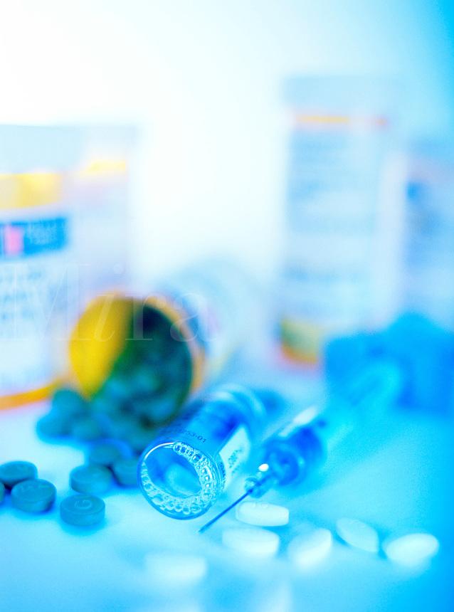 Close up of pills, pill bottles, vials and a needle.