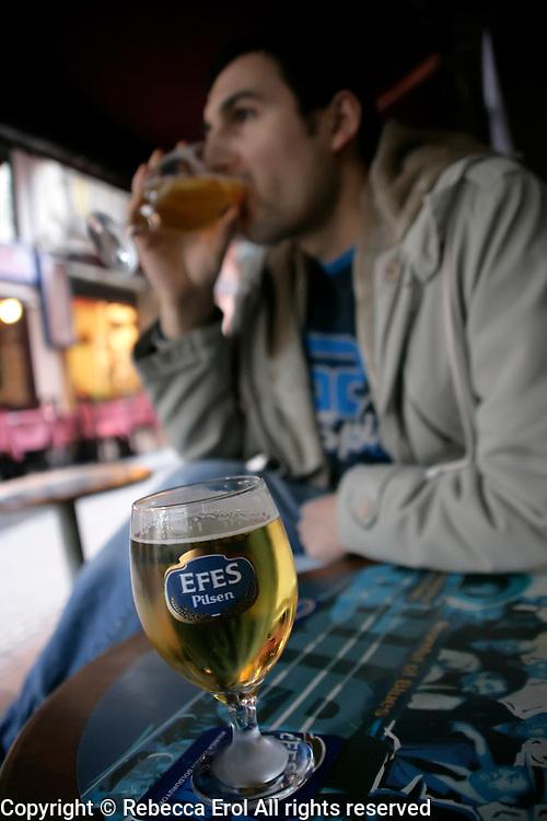 Turkish man drinking Efes beer in Taksim, Istanbul, Turkey
