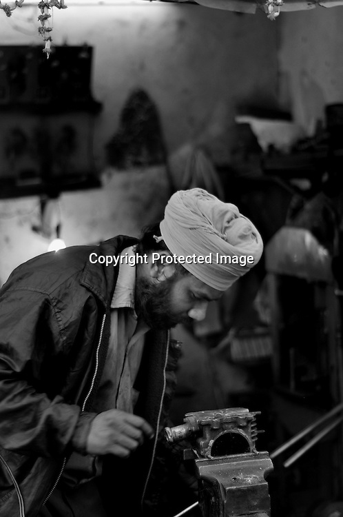 Balbant Singh was only 5 years when his father and brother were killed in the Sikh Genocide of 1984. He missed education due to poverty and started working as a child labour.  Now, with hard work, he has established a small mechanical workshop. He is the sole earning member in a big family and stays in the widow colony of Tilak Bihar. Tilak Vihar in New Delhi is called the widow colony. Widows and children of the Sikhs who were killed in 1984 Sikh Genocide live here. Four thousand Sikhs were killed in 72 hours in Delhi alone but no body till date has been punished for such an inhuman crime. Illiteracy, drug addiction, child labour and immense poverty characterize the area. Twenty five years ago all the male family members above the age of 15 were killed and burnt, leaving their uneducated widows and children behind to suffer, even after 25 years. The present generation is jobless, steeped in alcoholism and have lost their directions in life. November 2009. New Delhi, India, Arindam Mukherjee