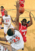 Dec. 07, 2010; Charlottesville, VA, USA;  Radford Highlanders guard Jareal Smith (4) shoots between Virginia Cavaliers forward Akil Mitchell (25) and Virginia Cavaliers forward Mike Scott (23) during the game at the John Paul Jones Arena. Virginia won 54-44. Mandatory Credit: Andrew Shurtleff