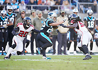 CHARLOTTE, NC - NOVEMBER 17: De'Vondre Campbell #59 and Kendall Sheffield #20 of the Atlanta Falcons try to tackle Christian McCaffrey #22 of the Carolina Panthers during a game between Atlanta Falcons and Carolina Panthers at Bank of America Stadium on November 17, 2019 in Charlotte, North Carolina.
