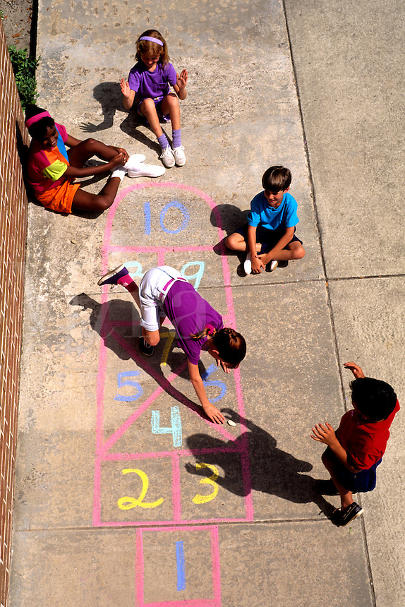 Mixed ethnic children playing hopscotch on sidewalk at school or playgroun