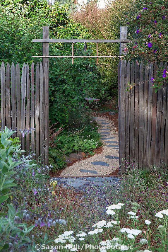 Entry gate through fence to pathway with stepping stones on permeable gravel; California native plants, Heath-Delaney garden
