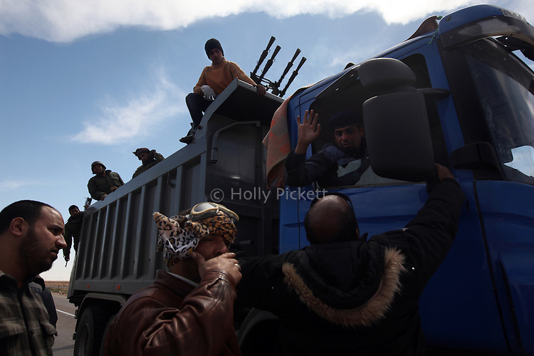 Opposition fighters with an anti-aircraft canon prepare to cross a checkpoint near Al Uqaylah, Libya, March, 12, 2011. The rebels continued to lose ground against loyalist forces of Col. Muammar Qaddafi and were attacked from the air, the sea and the ground.