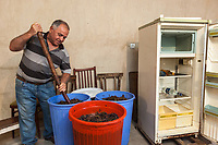 Armenia. Ararat Province. Byuravan. After harvest, <br /> Ishkhan Arakelyan mixes grapes with a wooden stick  inside large plastic buckets. The goal is to let grapes ferment and later distil an alcohol (raisin/grape spirit) to a maximum of 94.55% abv. Byuravan is a village located in the Ararat Province. 1.10.2019 © 2019 Didier Ruef