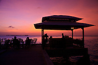 Tourists enjoy sunset / dusk from the deck chairs and bar on the end of the dock at Wakatobi Dive Resort, Southeast Sulawesi, Indonesia.