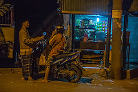 Bali, Indonesia.  Two Men Talking at Night  outside a Refreshment Stand.  Klungkung, Semarapura.