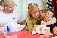 Jonathan Maul gets some help during art and crafts time at the Share and Care Network's annual retreat held at the Doubletree Guest Suites Hotel in Boston on May 20, 2006. <br /> <br /> The Share and Care Network was created in 1981 by Pat Cahill when her son Scott was diagnosed with Cockayne Syndrome.  A rare form of dwarfism, Cockayne Syndrome is a genetically determined condition whose symptoms include microcephaly, mental retardation, progressive blindness, progressive hearing loss, premature aging, and a shortened lifespan averaging 18 years.  Those afflicted have distinctive facial features, including sunken eyes, pinched faces, and protruding jaws as well as distinctive gregarious, affectionate personalities.<br /> <br /> Because of the rarity of the condition (1/1,000 live births) and its late onset (characteristics usually begin to appear only after one year), many families and physicians are often baffled by children whose health begins to deteriorate after normal development.  It was partly with this in mind that the Share and Care Network was formed, to promote awareness of this disease as well as to provide a support network for those families affected.  In 1998 it began organizing an annual retreat, which has grown from three families in its inaugural year to more than 30 today.  Although the retreat takes place in the United States, families from as far as Japan arrive for this one weekend out of the year to share information and to support one another.
