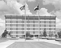 Completed 6-story library at University of Texas at Arlington; cars parked along street outside the building, ca. late 1967