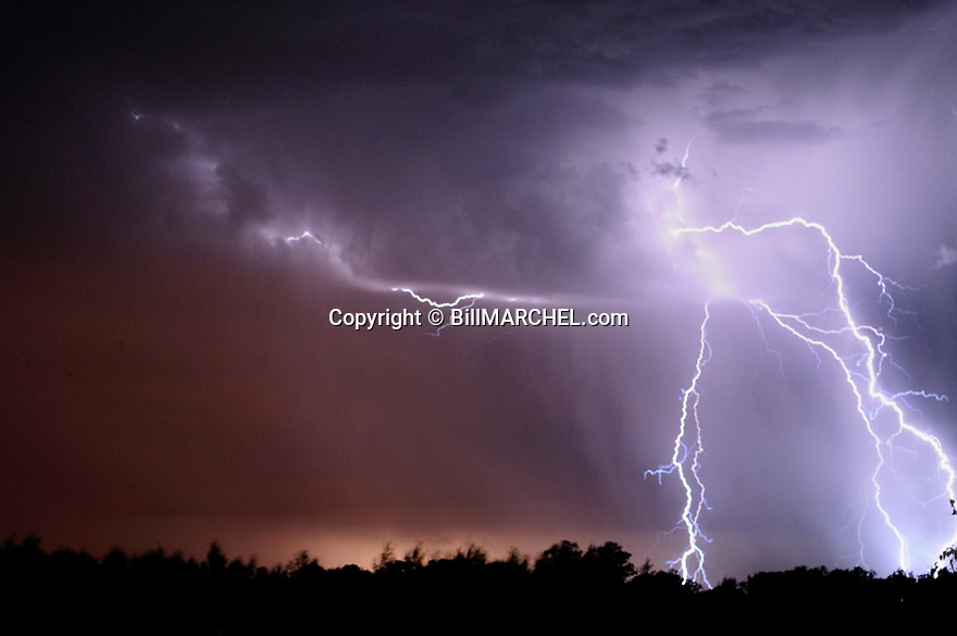 00715-004.01 Lightning bolts jut from a slight crimson sky.  Storm, thunder, rain.