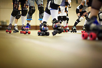 Skaters doing laps at a roller derby practice in Wilmington, Massachusetts. Roller derby is an American contact sport, popular with young women, which combines both athleticism and a satirical punk third-wave feminism aesthetic.