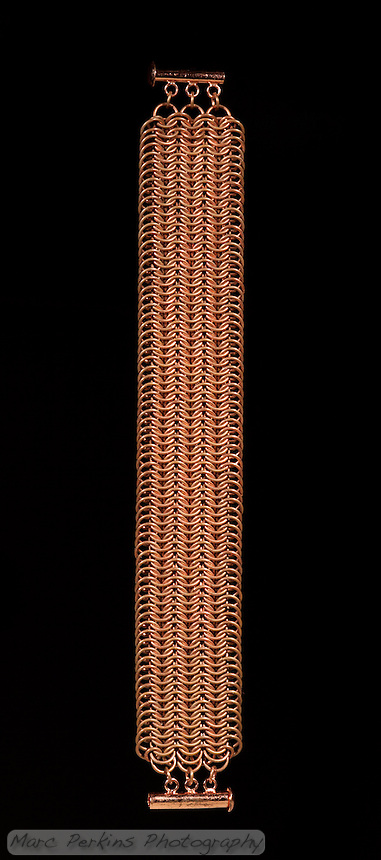 A european 8-in-1 copper chainmail bracelet with a sliding clasp made by Michelle.  The rings are 20 gauge 3/16 copper.   The project is illuminated using two off-camera flashes setup to create a natural black background behind the work.