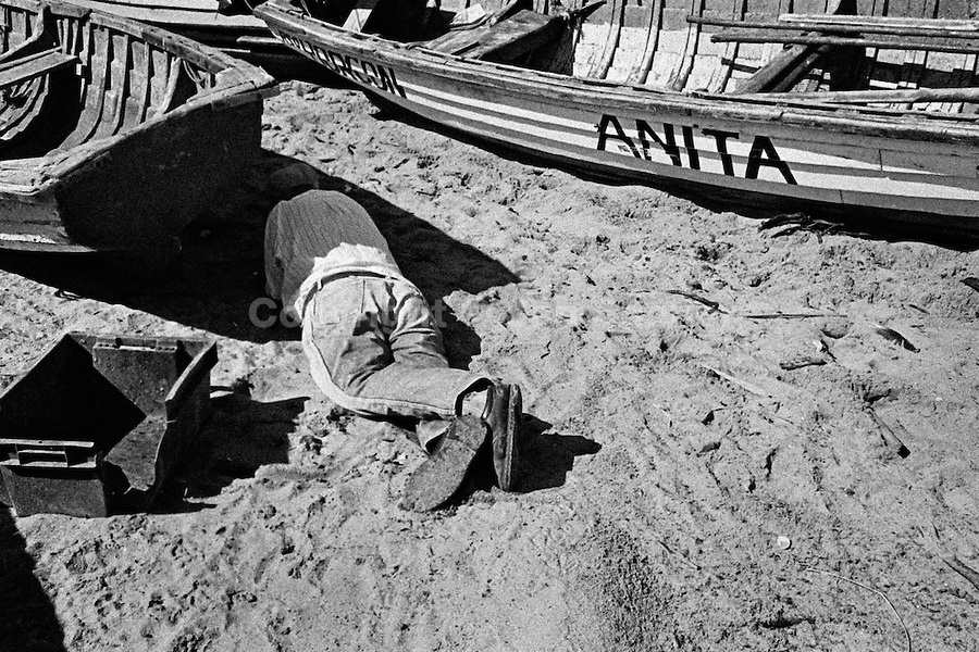 A Chilean fisherman, after drinking a couple of pisco shots, rests in the shadow of his boat on the beach of Quintero, Chile, 19 April 2002.