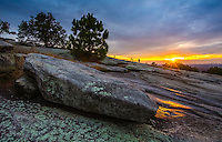 Landscape Scenic photograph of a spectacular sunset that reveals a starburst effect of light rays falling onto the summit of Stone Mountain which is located in the beautiful state of Georgia. <br /> The unique golden rays of the sun spread textured light beams of colors across the rocky surface of this granite mountain.