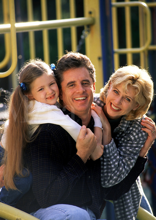 A smiling young girl, her mother and father play on playground equipment.