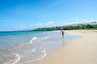 Woman in hat running along Hapuna Beach, along the Big Island's Kohala Coast. This white sand beach has been rated one of the best beaches in the world time and time again.