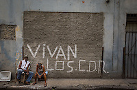 Havana, Cuba, sept 2014. A written on a wall says: long live the Revolutionary Defense Committee. These Comite exist in every block of the country. Its function is to ensure that the principles of the revolution are maintained and that no subversive movements are formed.In recent years, Raul Castro has made several economic measures for the people of the island. Cubans can now buy and sell apartments or cars, can stay in hotels on the island and can travel abroad with minor difficulties. Most of the global economists believe that these changes are moving in the right direction but its positive effects on people are very slow. Cubans continue to struggle daily through the streets of Havana with humor and zest for life.                                  En los ultimos años Raul Castro ha realizado varias medidas economicas para el pueblo de la isla. Ahora los cubanos pueden comprar y vender departamentos o coches, pueden alojarse en hoteles de la isla y pueden viajar al extranjero con menores dificultades. La mayor parte de los economistas mundiales consideren que estos cambios se mueven en la justa direccion pero sus efectos positivos sobre la gente son muy lentos. Los cubanos siguen luchando a diario por las calles de La Habana con humorismo y ganas de vivir.