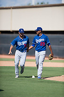 Los Angeles Dodgers relief pitcher Guillermo Zuniga (29) congratulates first baseman Meaux Landry (33) after making a great play during an Instructional League game against the Milwaukee Brewers at Maryvale Baseball Park on September 24, 2018 in Phoenix, Arizona. (Zachary Lucy/Four Seam Images)
