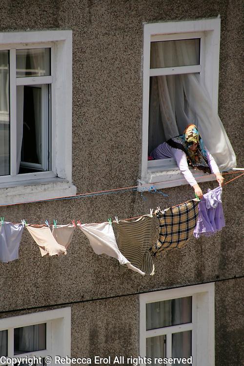 Woman putting out washing, Beyoglu, Istanbul, Turkey
