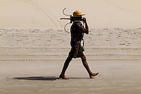 A Brazilian fisherman (jangadeiro) carries a handmade anchor on the beach of Iguape, Ceará state, northeastern Brazil, 14 March 2004. Jangadeiros, working on a unique wooden raft boat called jangada, keep the tradition of artisan fishing for more than four hundred years. However, being a fisherman on jangada is highly dangerous job. Jangadeiros spend up to several days on high-sea, sailing tens of kilometres far from the coast, with no navigation on board. In the last two decades jangadeiros have been facing up the pressure from motorized vessels which use modern, effective (and environmentally destructive) fishing methods. Every time jangadeiros come back from the sea with less fish.