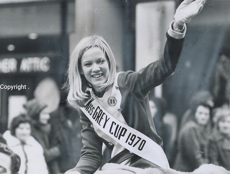 Miss Grey Cup; Nancy Durrell<br /> ; who came to Toronto as Miss Montreal Alouette; acknowledges the cheers of the crowds as the parade winds its way from Varsity Stadium to the Royal York Hotel. Chilly as it was for her; wearing a minidress in an open car in near-freesing weather for the three-hour parade; the Quebec blonde wears an Etobicoke Winter Carnival button urging Think Snow<br /> <br /> PHOTO :  Jeff Goode - Toronto Star Archives - AQP