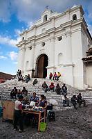 Chichicastenango, Guatemala.  Quiche Men Eating, Talking, and Resting on Steps of Santo Thomas Church.