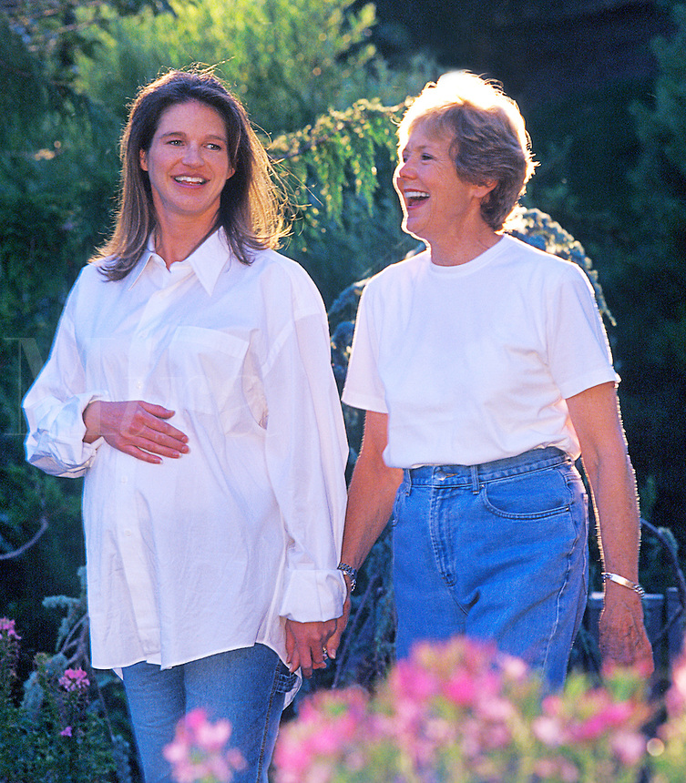 Pregnant expecting mother stolling with her mother in a garden