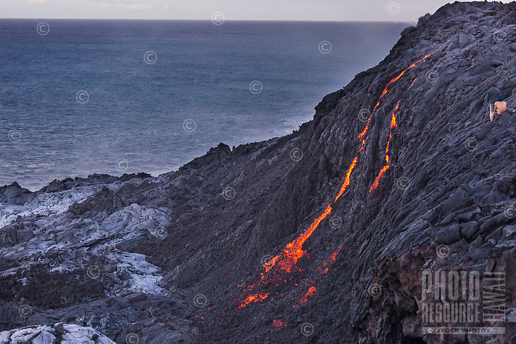 A couple sets up to take evening photographs of the lava flowing down a large cliff towards the ocean, Hawai'i Volcanoes National Park, Hawai'i Island.