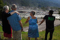 """Switzerland. Canton Graubunden. Bregaglia valley. Bondo. People look at a second massive landslide while the remote village is still recovering from a huge landslide caused by a giant rockslide swept down from Piz Cengalo on August 23, 2017. The four people who had returned to their homes had to be evacuated from the village for the second time. Silvia Rogati (L), 81 years old, puts her arm on the shoulder of a friend to confort both of them. The young man (R) wears a black t-shirt with the written words """" Youth Bregaglia"""". The mudslide smash the carpentry factory and equipment that was being used to clear debris from the previous landslide. The road had to be closed to traffic. 25.08.2017 © 2017 Didier Ruef"""